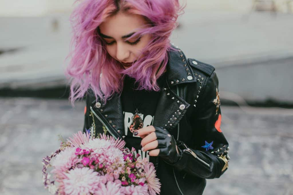 Woman with pink hair holding a bouquet of flowers